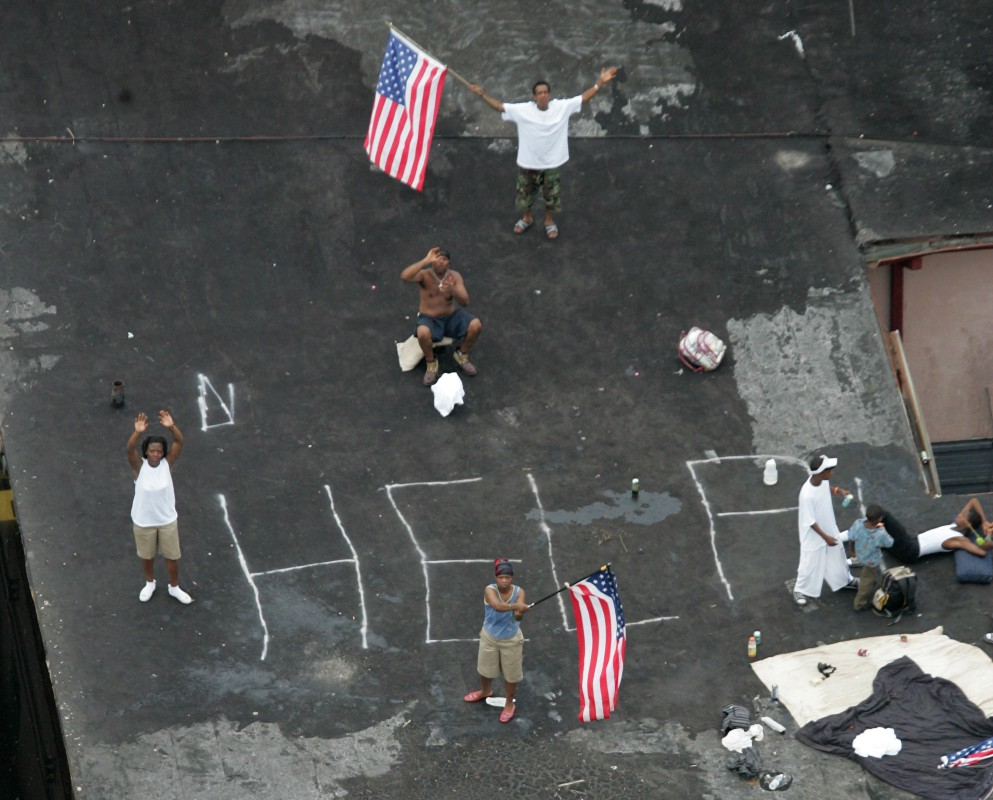 In this Sept. 1, 2005, file photo, residents wait on a rooftop to be rescued from the floodwaters of Hurricane Katrina in New Orleans. (AP Photo/David J. Phillip)