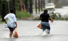 People carry bags of groceries through floodwaters after taking the merchandise away from a wind damaged convenience store in New Orleans on Monday, Aug. 29, 2005. (AP Photo/Dave Martin)